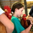 Emily Capps prepares to head out to the auction floor with one of the many roosters up for sale in a 4-H auction held Saturday at the WNC Agricultural Center. Animals formerly shown at the Mountain State Fair were auctioned to raise money for the clubs. 2012 file photo by Colby Rabon/Carolina Public Press