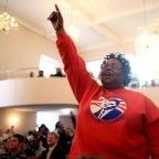 """Karen Cowan cheers and sings along to """"My God is Awesome,"""" which was led by Dr. Lamar Hylton during Monday's service at St. James AME Church in Asheville. The service was the start of the Annual Peace March and Rally held by the Martin Luther King Association of Asheville and Buncombe County. The association organized many events during the weekend in celebration of the Rev. Martin Luther King Jr. and his legacy. Colby Rabon/Carolina Public Press"""