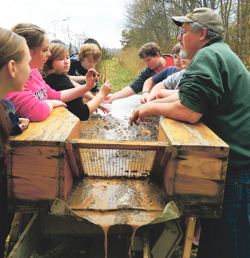 Yancey County School Board member Norb McKinney talks with middle school students at the Cane River archaeological site along the river where river cane will be be planted for Cherokee artisans to harvest. Photo courtesy of Yancey Common Times Journal.