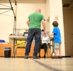 Morgan Murray and his 6-year-old son, Blue, check in at the polling station at Isaac Dickson Elementary in Asheville. Local races in Buncombe County included primaries for county commission, district attorney, clerk of superior court and district court judge. Colby Rabon/Carolina Public Press