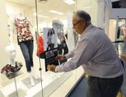 """Ray Soporowski, mall manager for Concord Mills, puts up a """"better than tax-free shopping"""" sign on the front window of the Dressbarn at Concord Mills this week. The Dressbarn will participate in the upcoming """"better than tax-free shopping"""" event Friday through Sunday. Robert Lahser/Charlotte Observer"""
