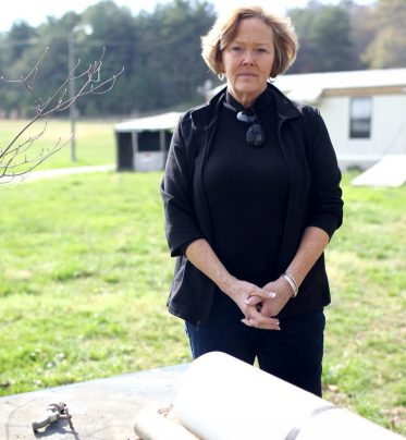 Jeri Cruz stands beside her deceased neighbor's well in Arden. The state has said not to drink the water due to contaminants. Colby Rabon / Carolina Public Press