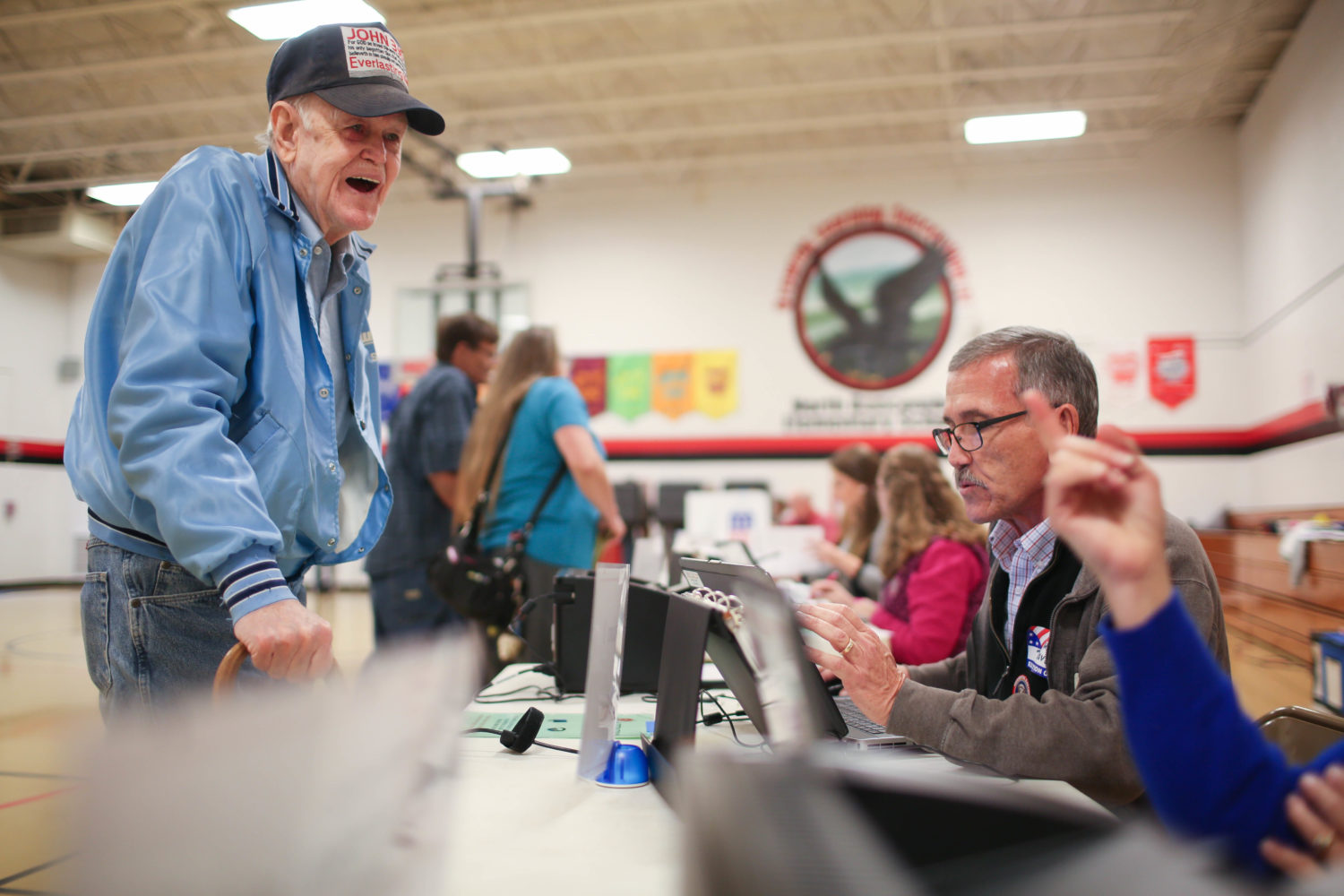 Joseph Brown laughs with election workers as he signs in to vote at North Buncombe Elementary School in Weaverville on Tuesday in 2016. Colby Rabon / Carolina Public Press