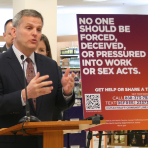 Josh Stein unveils anti-human-trafficking signs.