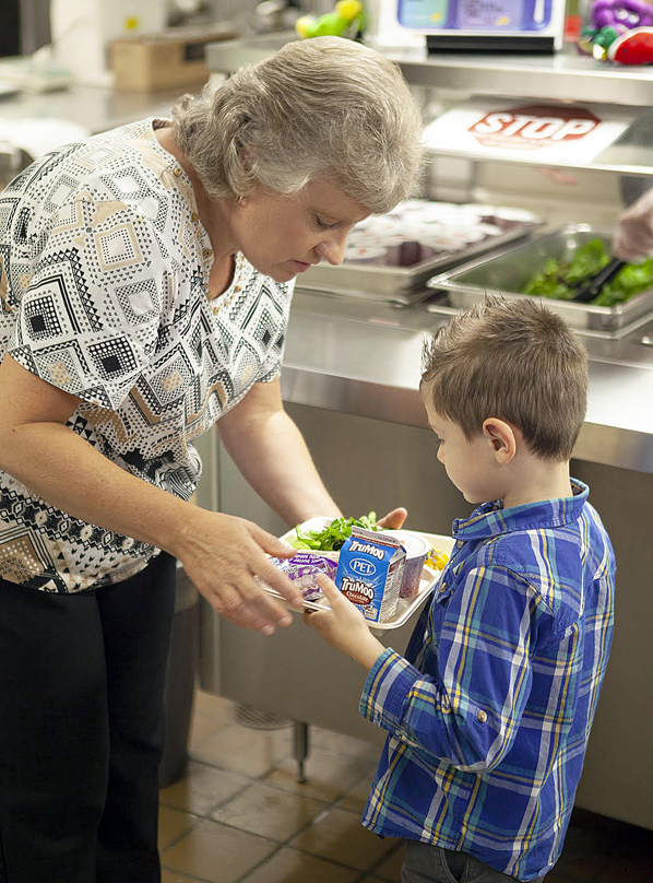 Teacher Wendy Stewart hands out meals to first-graders at Blue Ridge School in Cashiers.
