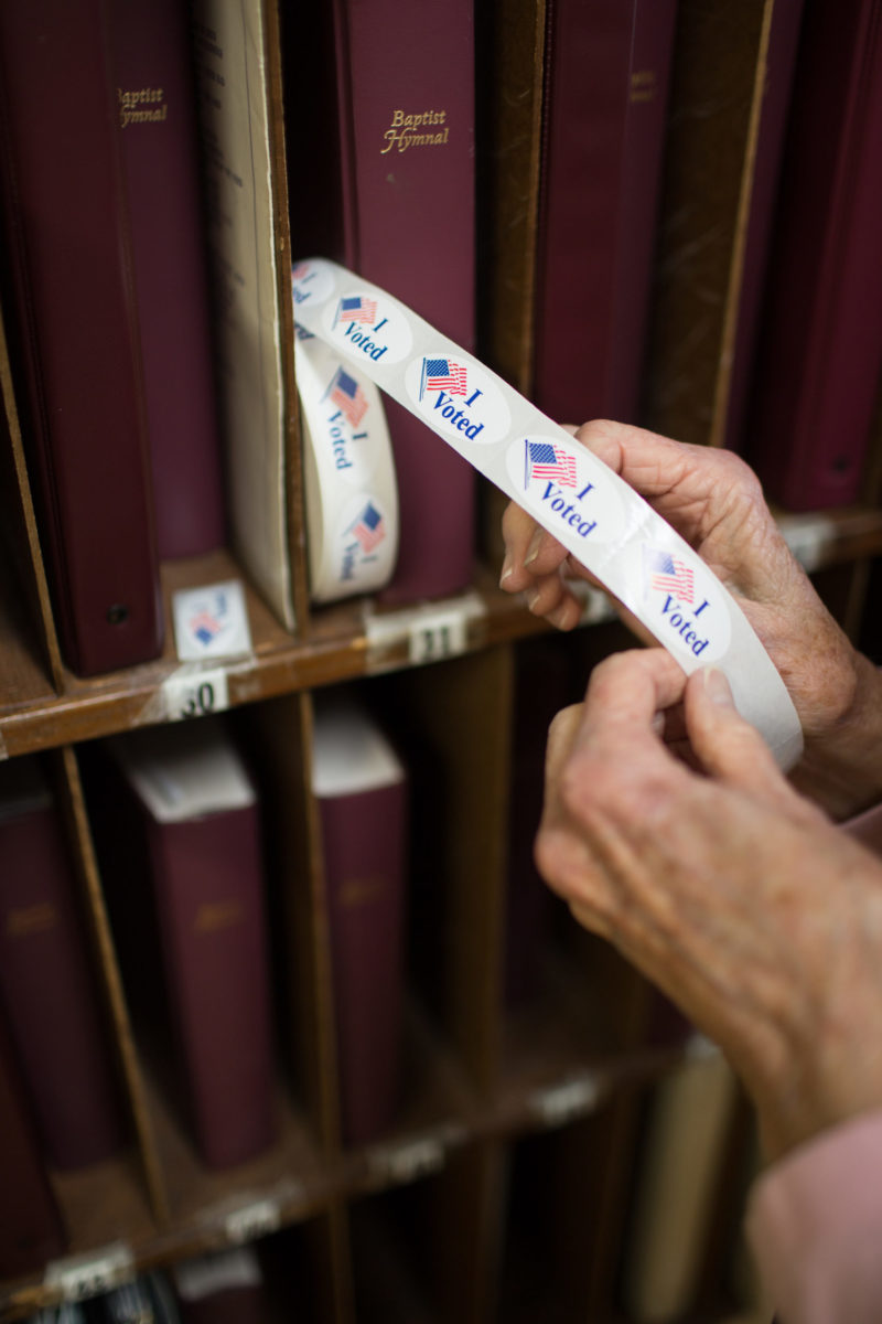 """An poll worker pulls out a """"I voted"""" sticker at the First Baptist Church of Black Mountain polling place in Buncombe County on March 3, 2020. Colby Rabon / Carolina Public Press"""
