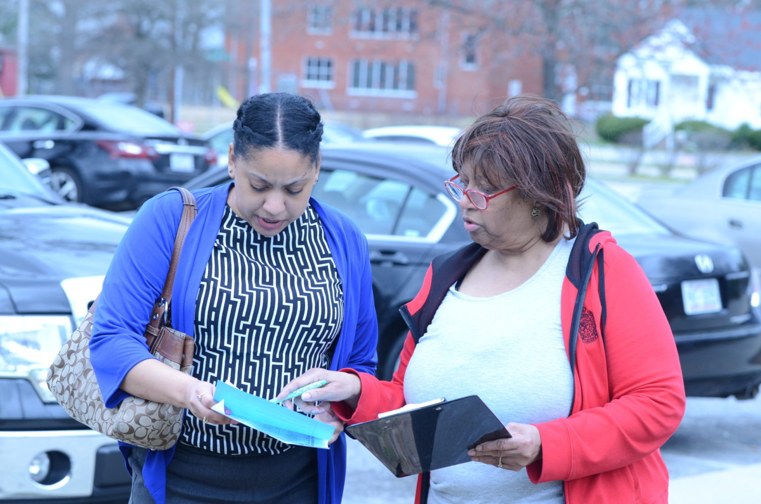 Carolyn Seward, right, representing the Democratic Women of Nash County, greets 2020 primary election voter Cassandra Williams as she arrives outside the Braswell Memorial Library polling place in Rocky Mount on March 3, 2020. Calvin Adkins / Carolina Public Press