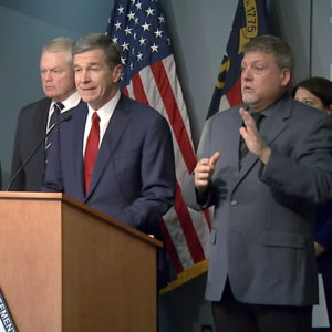 Roy Cooper announces confirmation of the first novel coronavirus case in North Carolina at a press conference on Tuesday. Courtesy of a screengrab from UNC-TV.
