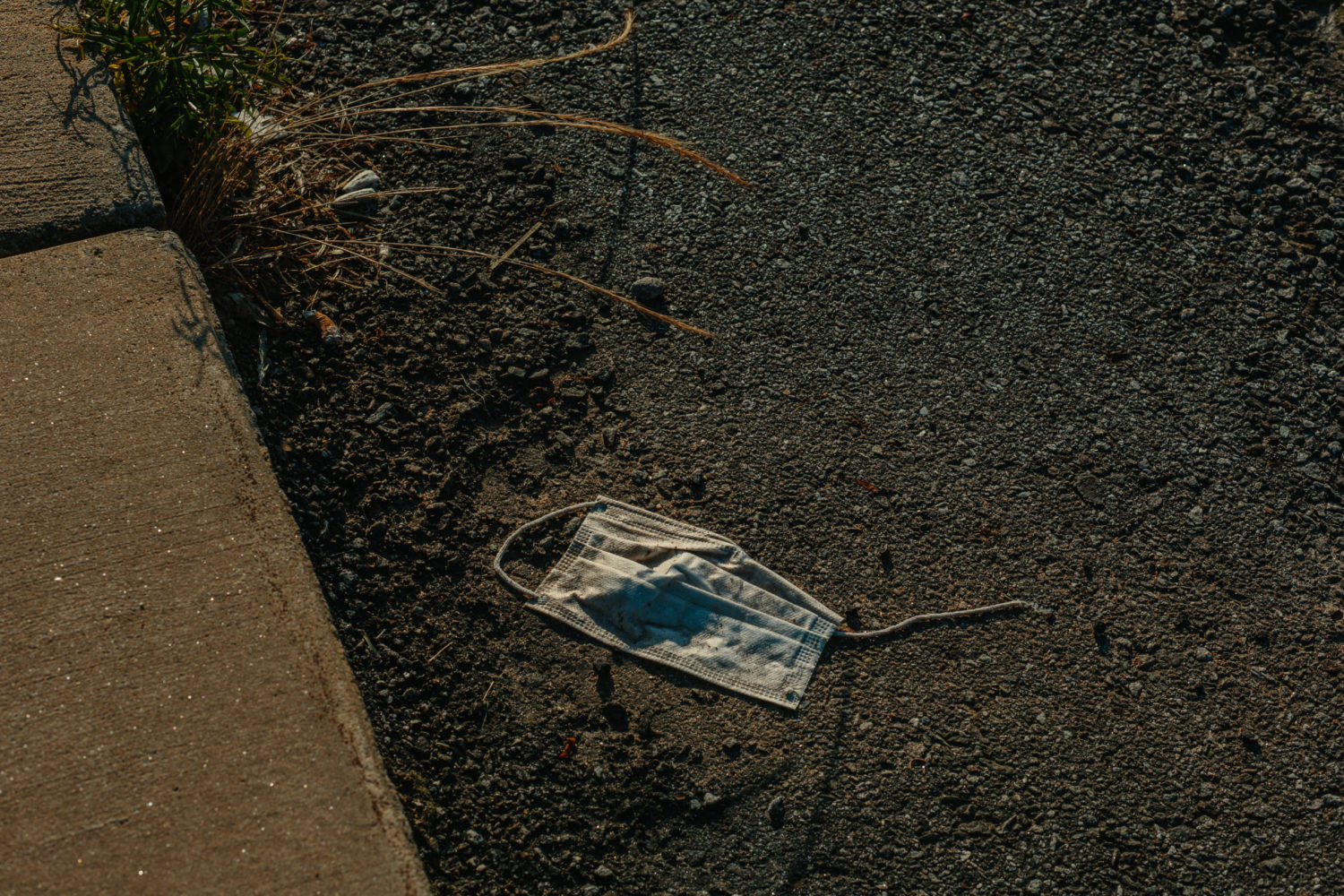 A discarded surgical mask lies in a parking lot near the Tyson processing facility in Wilkesboroon Sunday, May 24, 2020. At the plant, 570 workers have tested positive for the coronavirus. It's one of several outbreaks at meatpacking plants across the state. CREDIT: Jacob Biba for Carolina Public Press