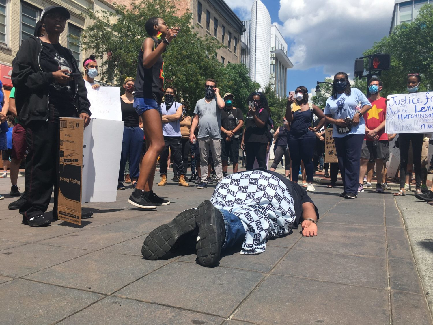 """Durham resident Mystic Waters, a.k.a. Chauncey Taylor, lay on the burning concrete and screamed, """"I can't breathe,"""" punctuating the points made by other protestors speaking to the crowd about racial injustice."""