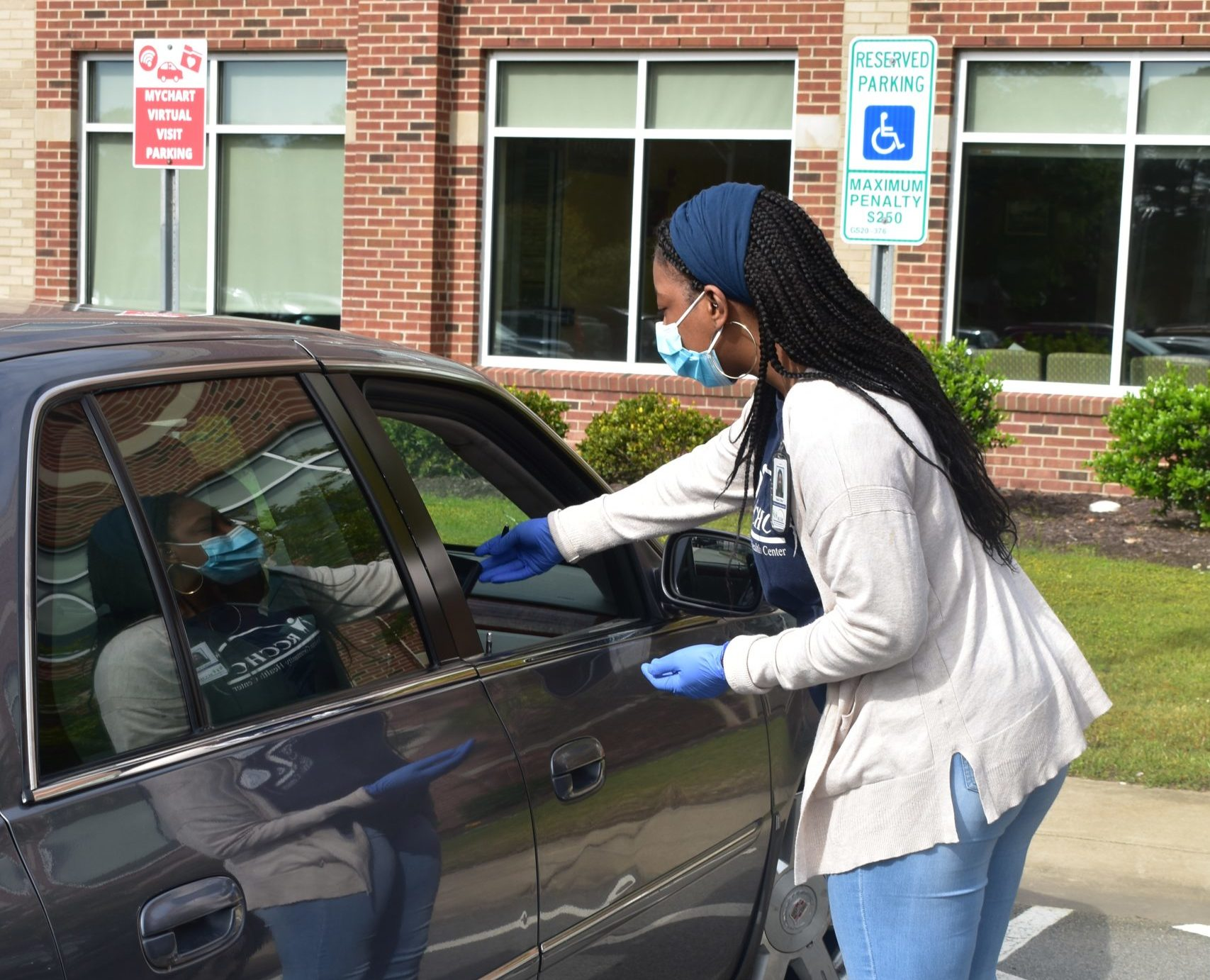 """In addition to referring its patients to needed social services through the new NCCARE360 portal, Roanoke Chowan Community Health Center is holding """"virtual visits"""" in its parking lot so patients can engage in social distancing. Here, staff member Nesita Britt delivers a mobile device so a patient can speak with a provider."""